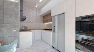 Białą kuchnię ocieplił jasny odcień drewna. Między blatem a szafkami jest biały lacobel. Dwie odmienne głębokości szafek wiszących pozwoliły zaoszczędzić więcej potrzebnego w kuchni miejsca.