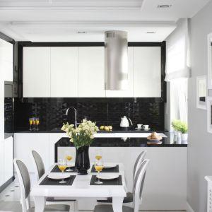 Czerń i biel to bardzo stylowe połączenie kolorów. Aby optycznie nie zmniejszyć małej kuchni, warto wybrać taką kolorystykę w formie połyskujących powierzchni. Projekt: Katarzyna Mikulska-Sękalska. Fot. Bartosz Jarosz