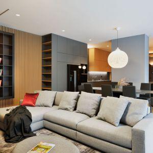 Elegancki apartament z otwartą strefą dzienną widoczną z holu, urządzono w harmonizujących kolorach grafitowej szarości i ciepłego drewna. Projekt: GAO Arhitekti. Fot. Miran Kambic