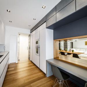 Przy oknie zaplanowano blat, pełniący funkcję stołu jadalnianego. Projekt: Brain Factory – Architecture & Design. Fot. Marco Marotto