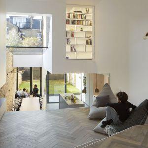 Dzięki temu powstała oryginalna przestrzeń, w której wychodząca na ogród kuchnia widoczna jest z poziomu położonego wyżej salonu, z którego można również spoglądać na przeszkloną biblioteczkę na półpiętrze. Projekt: Scenario Architecture. Fot. Matt Clayton