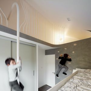Wykorzystując do maksimum wszelkie nisze i wnęki w domu, urządzono oryginalny pokój zabaw dla dzieci ze ścianką wspinaczkową. Projekt: Scenario Architecture. Fot. Matt Clayton