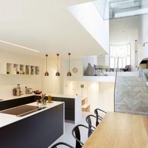 Centrum wnętrza stanowi otwarta, wielopoziomowa przestrzeń, powstała z połączenia oryginalnych dwóch wiktoriańskich salonów na froncie domu, z piwnicą znajdującą się całe piętro niżej, tak, aby pomieszczenia przenikały się fizycznie, jak i wizualnie. Projekt: Scenario Architecture. Fot. Matt Clayton