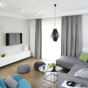 Jasne wnętrze w nowoczesnym stylu, zaaranżowane w bieli i szarościach. Fotel w kolorze turkusowym oraz szare pufy wyznaczają styl wnętrza oraz dodają mu smaku. Projekt: Małgorzata Galewska. Fot. Bartosz Jarosz