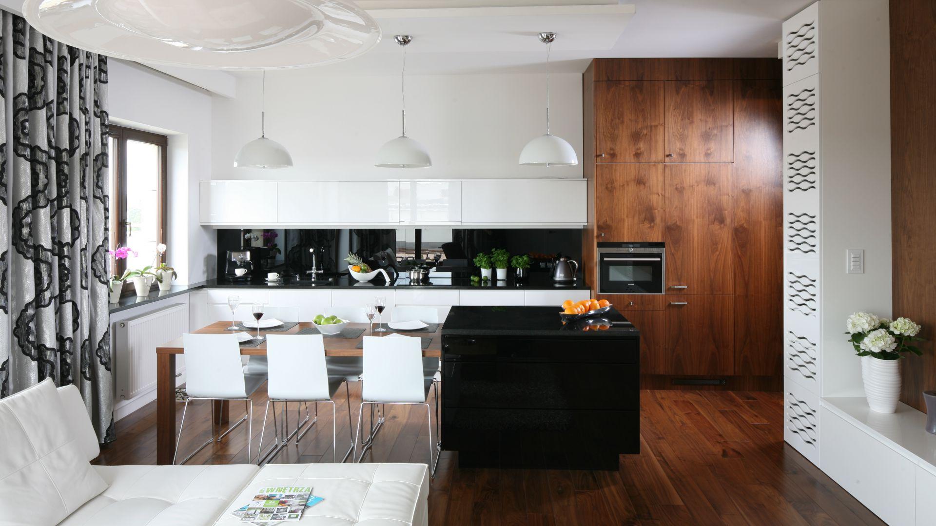 Elegancka, biała kuchnia w nowoczesnym stylu. Drewniana zabudowa pod sam sufit nawiązuje do stylu w salonie. Projekt: Agnieszka Ludwinowska. Fot. Bartosz Jarosz