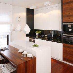 Fornirowane powierzchnie są łatwe do utrzymania w czystości. Ocieplają również białą kuchnię. Projekt: Katarzyna Kiełek, Agnieszka Komorowska - Różycka.