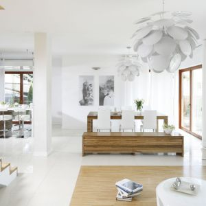 To białe, minimalistyczne wnętrze zdobi drewno. Kuchnia ulokowana został nieco na uboczu, natomiast strefę salonu i jadalni wyodrębniają inne wykończenia podłogi - płytki lub drewno. Projekt: Agnieszka Ludwinowska. Fot. Bartosz Jarosz