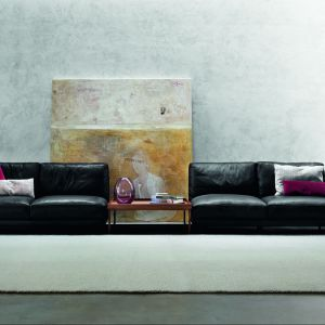 Sofa Swanday marki Swan wygląda jakby została rozerwana na pół. Pomiędzy dwa elementy siedziska został wstawiony niski, nowoczesny stolik. Fot. Swan
