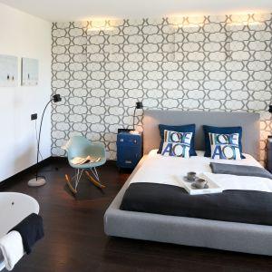 Szare łóżko w zestawieniu z dekoracyjną tapetą oraz niebieskimi szafkami nocnymi prezentuje się bardzo gustownie. Projekt: Justyna Smolec. Fot. Bartosz Jarosz