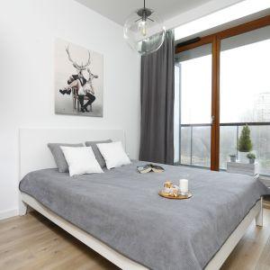 Sypialnia zaaranżowana w biało-szarej tonacji. Białe łóżko z drewnianą ramą idealnie wtapia się w aranżacyjną całość wnętrza. Projekt: Ola Kołodziej, Ula Szmyt. Fot. Bartosz Jarosz.jpg
