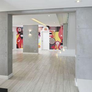 Jasne minimalistyczne wnętrze wypełnione białą i betonem ozdobiono wyjątkowo barwnymi grafikami. Projekt: Dominik Respondek. Fot. Bartosz Jarosz