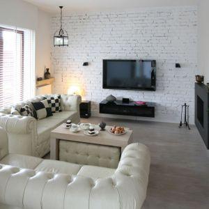 Ściana telewizyjna została wykończona cegłą pomalowaną na biało, co urozmaica ten nowocześnie urządzony salon. Projekt: Jarosław Jończyk. Fot. Bartosz Jarosz