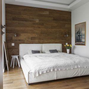Drewno na ścianie za łóżkiem nadaje aranżacji sypialni rustykalny ton. Projekt: Anna Nowak-Paziewska. Fot. Emi Karpowicz