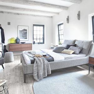 Szare łóżko Essence, na wysokich nóżkach. Poduszki na wezgłowiu można odpiąć co ułatwia ich czyszczenie. Fot. Swarzędz Home