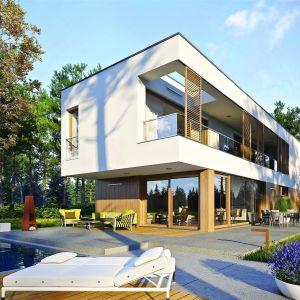 Atrakcyjna forma wyposażona w szerokie przeszklenia dodające bryle lekkości efektownie prezentuje się w śnieżnej bieli, wzbogaconej elementami drewna i soczystej zieleni, które podkreślają prestiż domu i pięknie korespondują z jego naturalnym otoczeniem.Dom EX 17 W2 Energo Plus. Projekt: Artur Wójciak. Fot. Pracownia Projektowa Archipelag