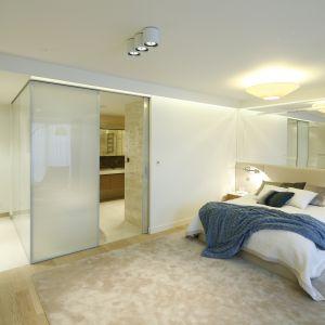 Sypialnia małżeńska z łazienką. Wnętrze urządzono w jasnych barwach. Duże łóżko zapewnia wygodę spania. Projekt: Anna Fodemska. Fot. Bartosz Jarosz