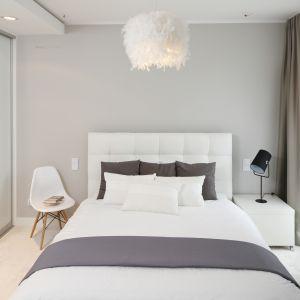 Elegancka sypialnia utrzymana w jasnej tonacji. Wnętrze ociepla dekoracyjna lampa nad łóżkiem oraz miękkie szare zasłony. Projekt: Małgorzata Galewska. Fot. Bartosz Jarosz