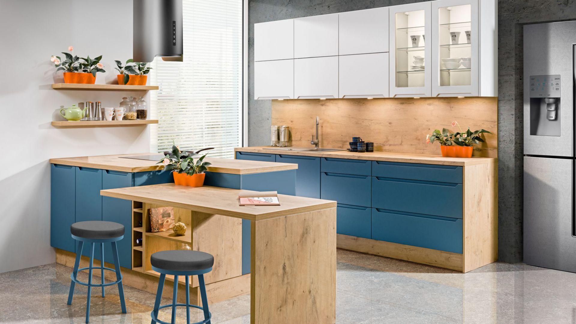 Dynamiczny niebieski w zestawieniu z jasnym drewnem, z wyraźnie zaznaczonym usłojeniem sprawia, że zabudowa kuchenna prezentuje się niezwykle efektownie. Fot. Spółka Meblowa KAM