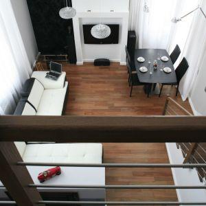 To wnętrze o stosunkowo niewielkim metrażu zyskało przestrzeń właśnie dzięki salonowi ciągnącemu się przez dwa piętra. Projekt: Michał Mikołajczak. Fot. Bartosz Jarosz