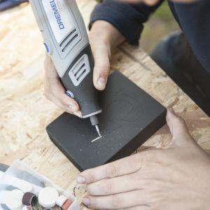 Wykorzystując narzędzie Dremel 7750 oraz końcówkę 107, zrób żłobienia obrysowując kontury.