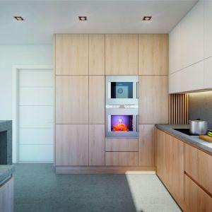 Ciekawym uzupełnieniem lekko loftowego betonu jest drewniana zabudowa kuchenna. Projekt: Dom w amorfach. Fot. Archon +