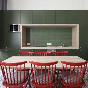 """W kuchni króluje minimalistyczna ciemnooliwkowa zabudowa, z którą korespondują klasycyzujące panele ścienne, a także wiśniowe krzesła """"patyczaki"""" polskiej firmy Fameg. Fot. GRID/Dekorian"""