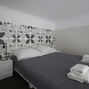 Szaro-białą sypialnię zdobi interesujący wzór na ścianie za łóżkiem. Fot. GRID/Dekorian