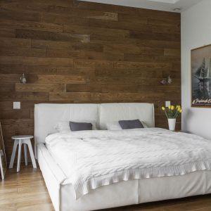 Ściana za łóżkiem wykończona drewnianymi deskami. Projekt: Anna Nowak-Paziewska. Fot. Emi Karpowicz