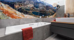 Utrzymana w biało-szarej tonacji łazienka ma oryginalny i dynamiczny wystrój. Klimat buduje tu tapeta z malowniczym górskim krajobrazem.