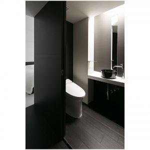 Toaleta, wzorem całego mieszkania, została utrzymana w monochromatycznej kolorystyce. Do pomieszczenia prowadzą przesuwne drzwi, dopasowane kolorystycznie do podłogi i sąsiadującej ściany nad toaletą. W oszczędnie wykończonej łazience, akcentem przyciągającym wzrok jest piękna czarna umywalka nablatowa. Fot. Koichi Torimura.
