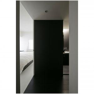 Z sypialni małżeńskiej jest bezpośredni dostęp do toalety. Po drugiej stronie przecinającej wnętrze po przekątnej ściany jest pokój gościnny, który w przyszłości zamieni się w pokój dla dziecka. Bliskie sąsiedztwo z sypialnią rodziców okaże się wtedy szczególnie praktyczne. Fot. Koichi Torimura.