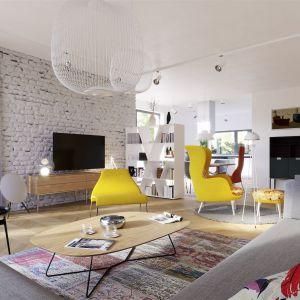 Uwagę zwraca dekoracyjna cegła tworząca atrakcyjne tło dla domowych wieczorów filmowych, a także optymistyczne, żółte fotele wnoszące do środka solidną porcję pozytywnej energii. Projekt: arch. Artur Wójciak. Fot. Pracownia Projektowa Archipelag