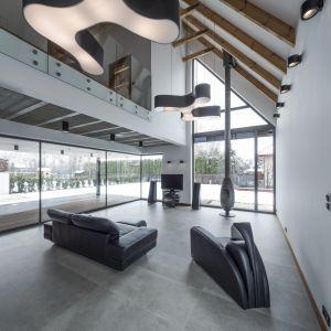 Dwukondygnacyjny salon z licznymi przeszkelniami jest niezwykle przestronny i pełen naturalnego światła. Wnętrze płynnie połączono z ogrodem, co zachęca do wypoczynku na tarasie podczas letnich dni. Fot. Beczak/Beczak/Architektci