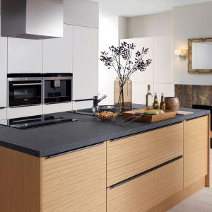 Wysoką zabudowę kuchenną w białym kolorze doskonale ociepla wyspa w kolorze drewna. Elegancji wnętrzu dodaje ciemny blat. Fot. Black Red White