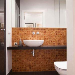 Ogromną ozdobą, definiującą charakter wnętrza, jest pięknie usłojona cedrowa mozaika, którą wyłożono ścianę za umywalką. Fot. MGN Pracownia Projektowa