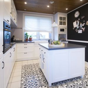 Kluczowym elementem kuchni jest wyspa na środku. Stylowa boazeria sufitowa, stylizowany piekarnik czy specjalnie zaprojektowane fronty szafek kuchennych, w pełni oddają ducha francuskiej krainy. Projekt: TWORZYWO studio. Fot. Jacek Gadaj