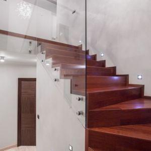 Szklana balustrada przy drewnianych schodach zamocowana z pomocą okuć Piemonte. Fot. CDA Polska