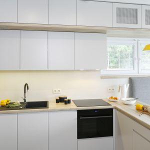 Nieskazitelną biel przełamują elementy drewna i soczyście żółta lampa. Projekt: Katarzyna Uszok-Adamczyk. Fot. Bartosz Jarosz