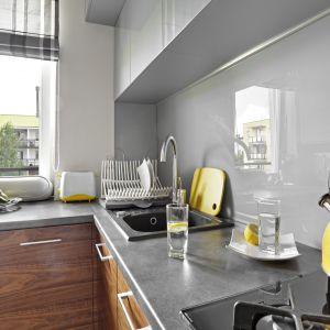 Wrażenie głębi w niewielkiej kuchni podkreślają szare fronty w połysku, które sięgają niemal pod sam sufit. Projekt: Ewelina Para. Fot. Bernard Białorudzki
