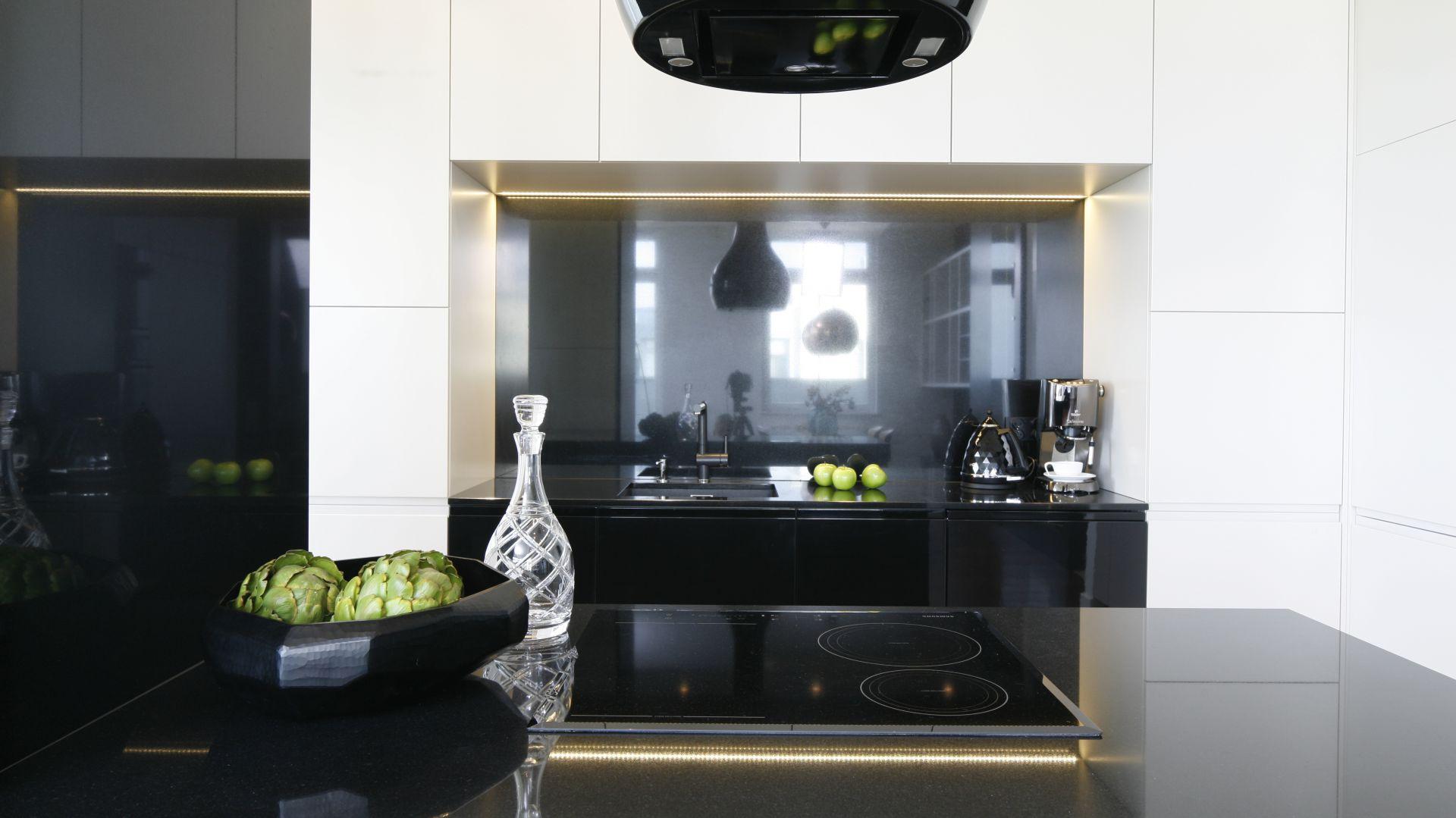 Mleczne fronty szafek kuchennych stanowią doskonały i wyrazisty kontrast dla czarnych granitowych blatów oraz jasnych, gresowych płytek podłogowych. Do całości pięknie pasuje czarny, wyspowy okap. Projekt: Agnieszka Hajdas-Obajtek. Fot. Bartosz Jarosz