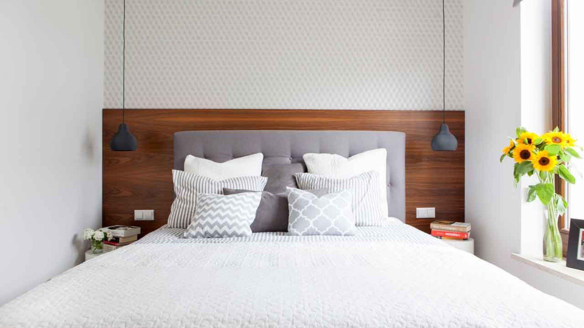 Przytulny nastrój  w tej sypialni tworzy drewno orzecha o ciepłej barwie, którym wyłożono ścianę za łóżkiem, a także miękkie tekstylia – tapicerowany zagłówek łóżka i leżące na nim poduszki o wzorach dopasowanych do ornamentu na tapecie. Z sufitu zwieszają się po obu bokach łóżka lampy na długich kablach, których nikłe światło tworzy wieczorem intymny klimat. Fot. Małgorzata Górska-Niwińska, MGN