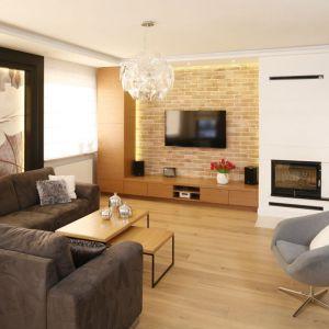 Klasycznie urządzone wnętrze dodatkowo zdobi ścianka telewizyjna wykończona cegłą. Małgorzata Mazur. Fot. Bartosz Jarosz