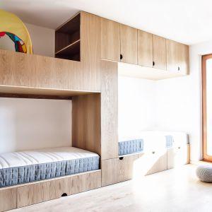 Każde łóżko z półeczką na książki i lampkę tworzy przytulny kącik zapewniający prywatność we wspólnej przestrzeni. Projekt:  Atelier Starzak Strebicki. Fot. Mateusz Bieniaszczyk