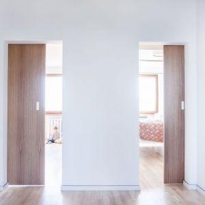 Zdecydowano się również zamienić tradycyjne skrzydło drzwi na przesuwany panel w kolorze mebli z płyty stolarskiej fornirowanej jesionem. Projekt:  Atelier Starzak Strebicki. Fot. Mateusz Bieniaszczyk