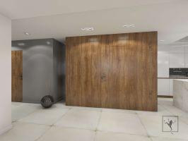 Od strony hallu kuchnię zamyka ściana wykończona pięknym drewnianym fornirem. Projekt: Marcin Gałuszka, Marcin Janus, Frog Studio