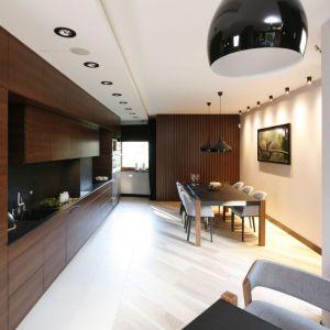 W tej nowoczesnej jadalni połączonej z kuchnią, nad stołem górują nowoczesne czarne lampy. Projekt Jan Sikora. Fot. Bartosz Jarosz