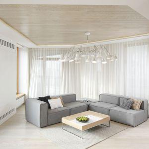 Białe wnętrze z szarą kanapą i nutką drewna. Projekt: Maciej Brzostek. Fot. Bartosz Jarosz