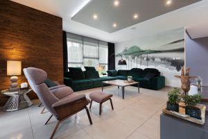 Piętrowy dom nad jeziorem w Margoninie. Wnętrze zachowane w modnych szarościach z elementami drewna. Na uwagę zasługuje piękna welurowa sofa w modnym szmaragdowym kolorze.