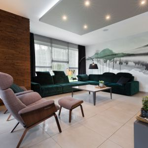 Piętrowy dom nad jeziorem w Margoninie. Wnętrze zachowane w modnych szarościach z elementami drewna. Na uwagę zasługuje piękna welurowa sofa w modnym szmaragdowym kolorze. Projekt: Edyta Wełnicka / ewem Aranżacja wnętrz