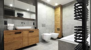 Urządzonej w minimalistycznym stylu łazience nie brak zarówno industrialnego pazura, jak i domowego ciepła. Połączenie faktur drewna i betonu z oszczędnymi formami wyposażenia pozwoliło stworzyć wnętrze przytulne i efektowne.